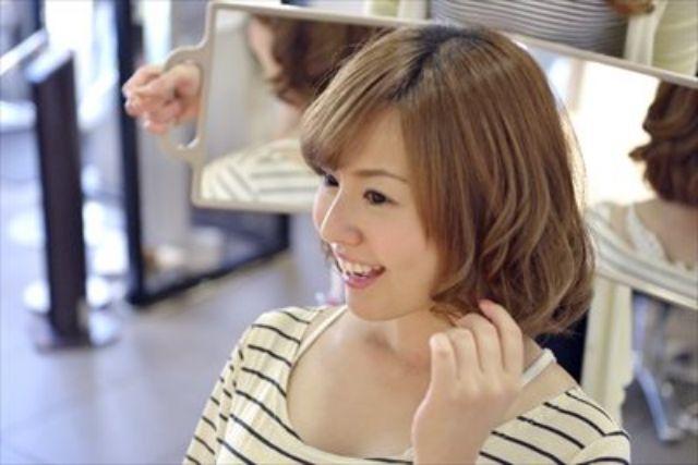 サロンで髪の毛を見る女性
